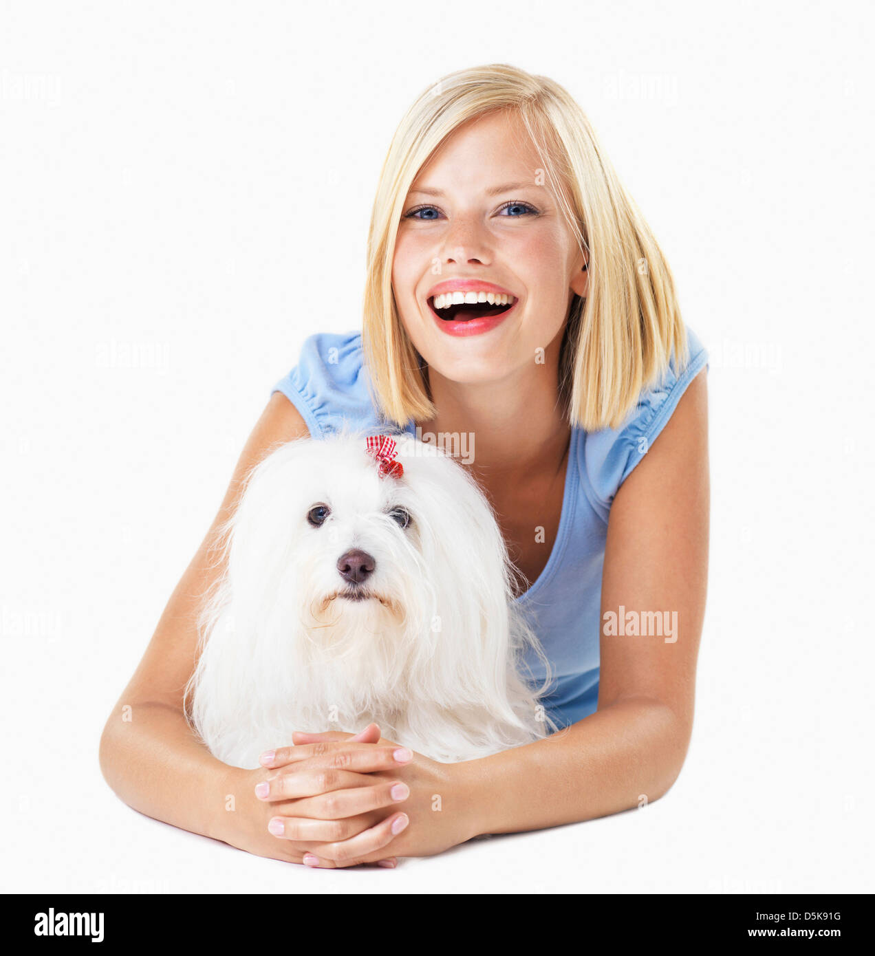 Studio Shot, Portrait of smiling young woman lying down with her dog - Stock Image