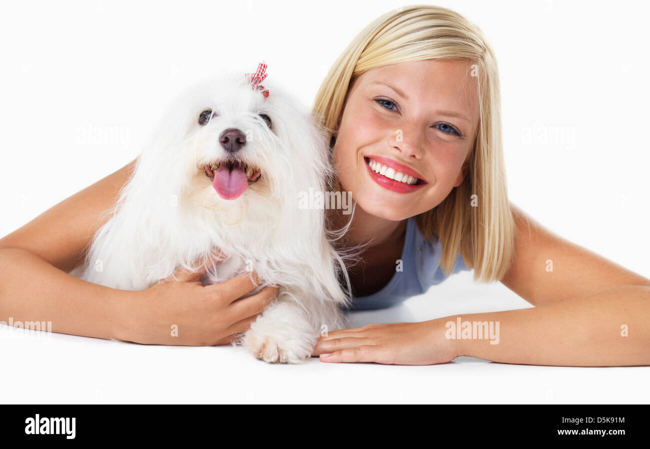 Studio Shot, Portrait of smiling young woman with her dog - Stock Image