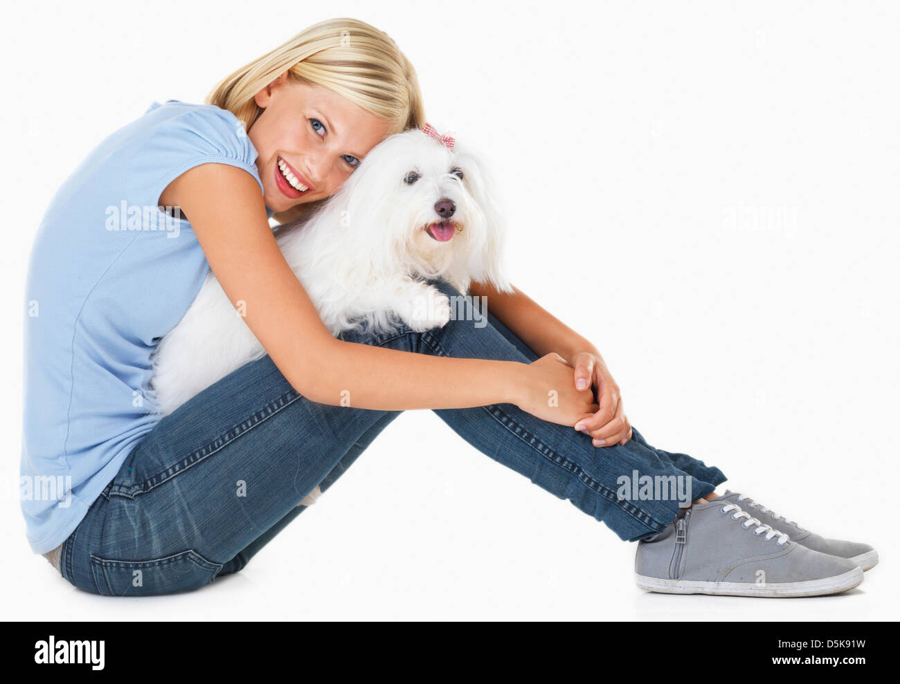 Studio Shot, Portrait of young woman sitting and holding dog - Stock Image