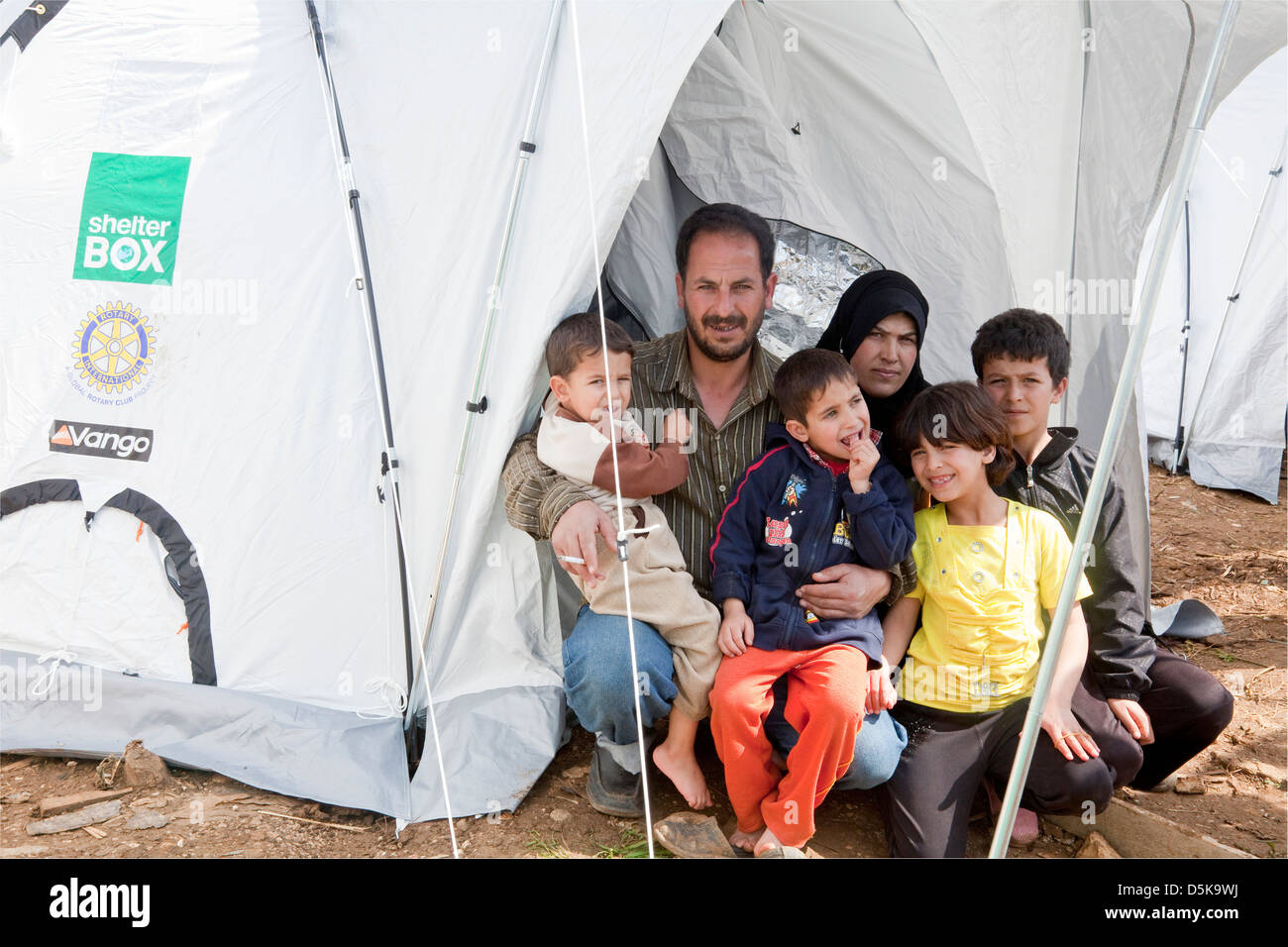 Refugee family, from Homs at a makeshift refugees camp in El Minie, NE Lebanon with their new ShelterBox tent - Stock Image