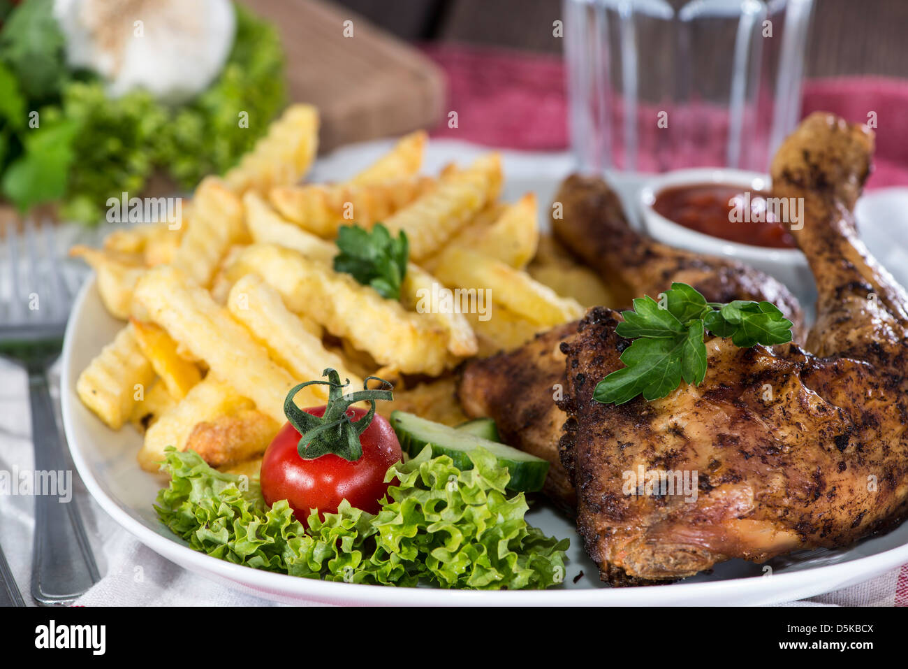 Grilled Chicken Legs with Chips and Sauce - Stock Image
