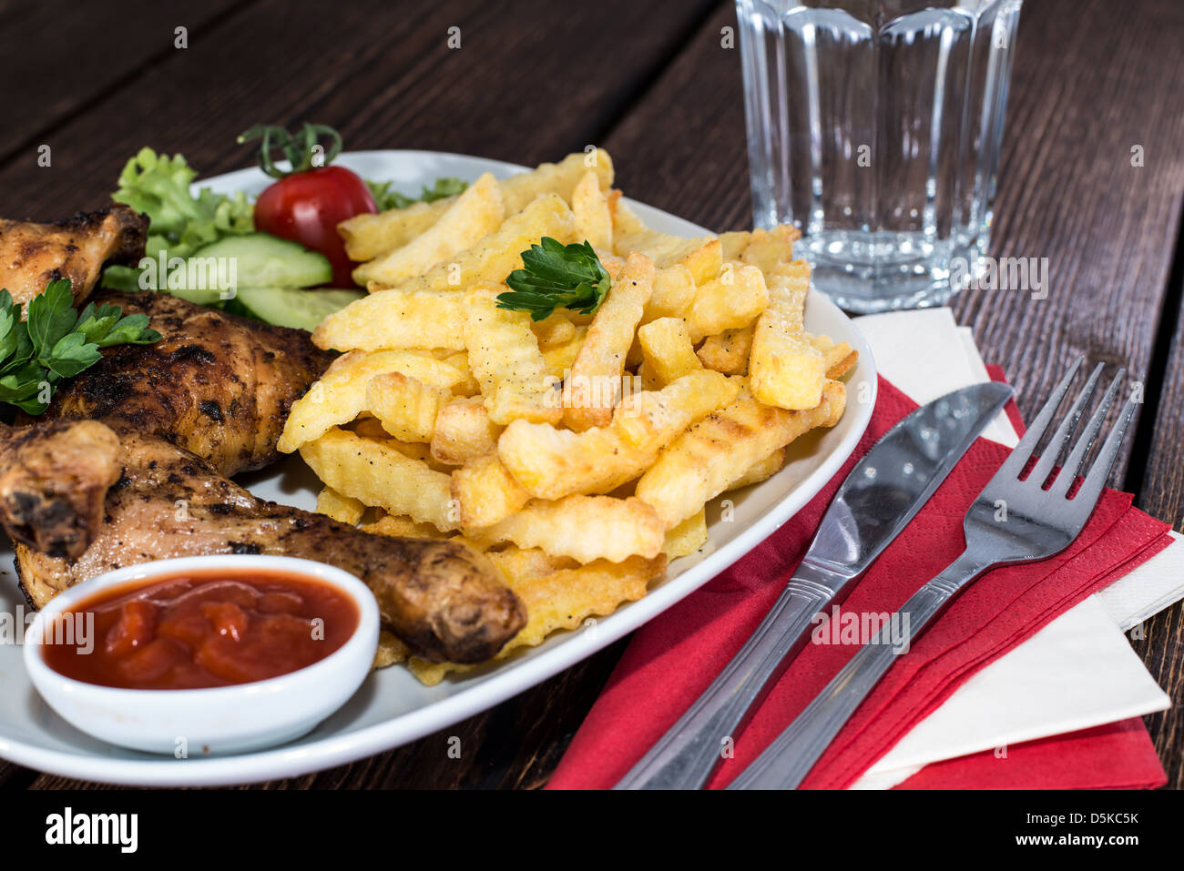 Portion of grilled Chicken Legs with Chips - Stock Image