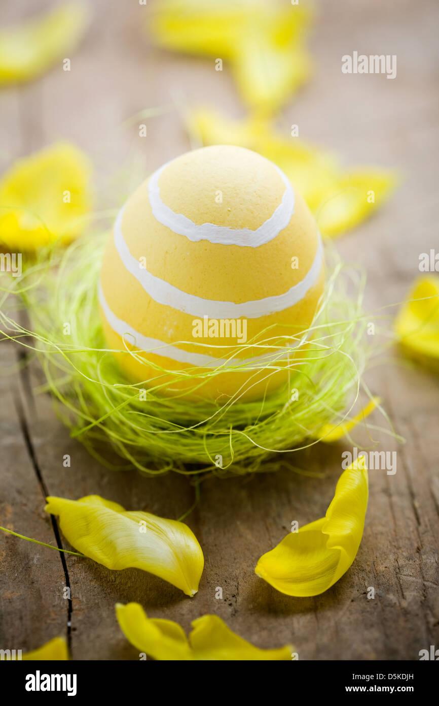 Painted easter egg in little green bird nest - Stock Image