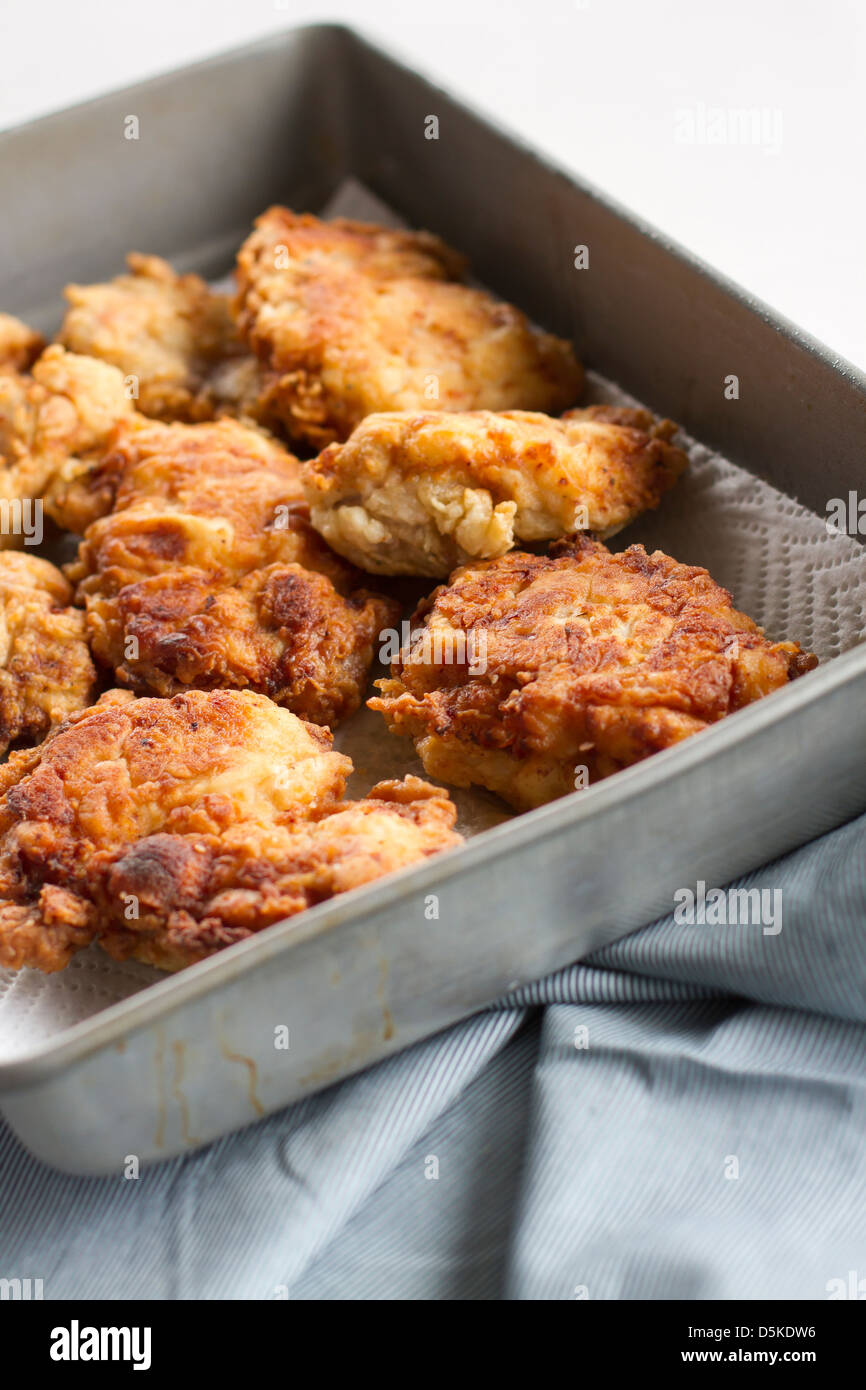 Several pieces of fried chicken in a pan. - Stock Image