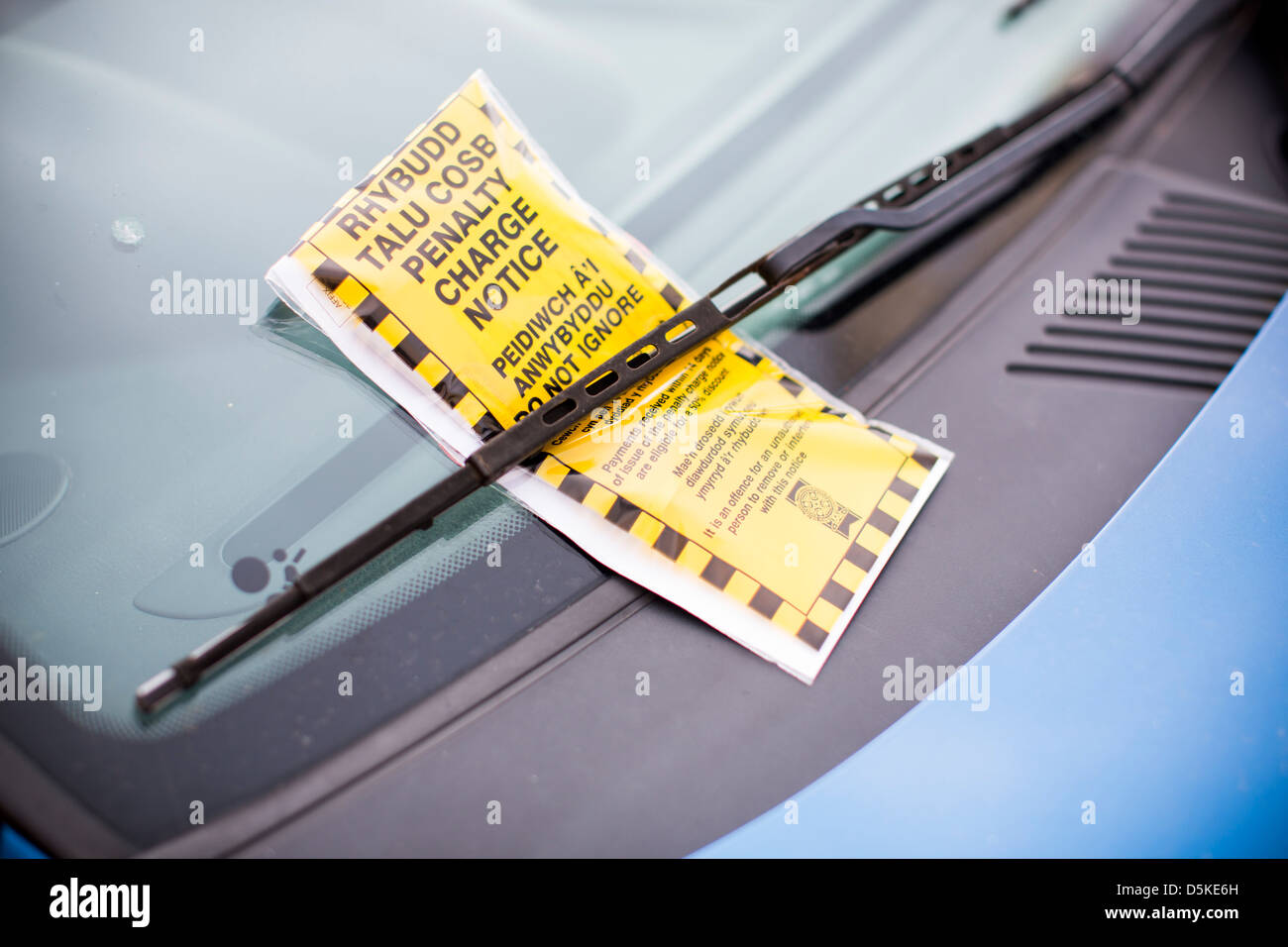 A bilingual penalty charge notice parking ticket in both English and Welsh beneath a car windscreen wiper. - Stock Image