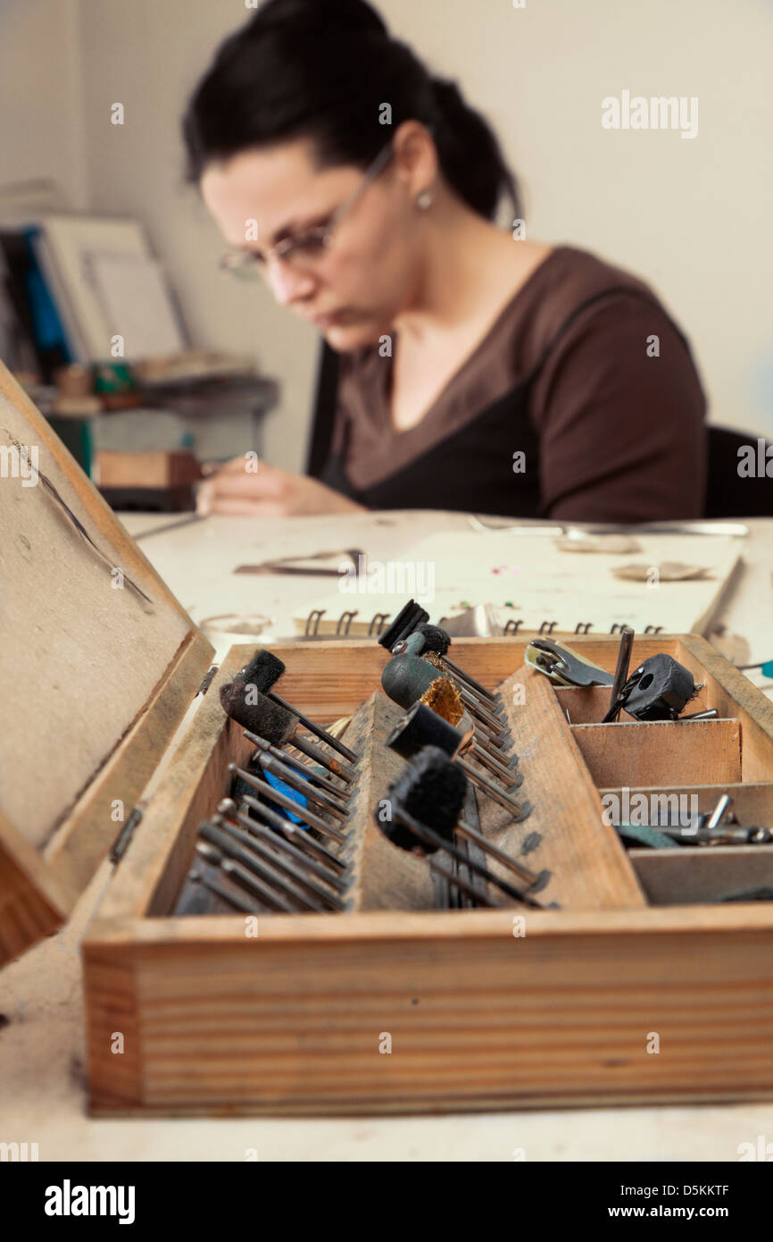 Selective focus on the opened wooden toolbox , in front of a femeale jeweler working in her workshop. - Stock Image