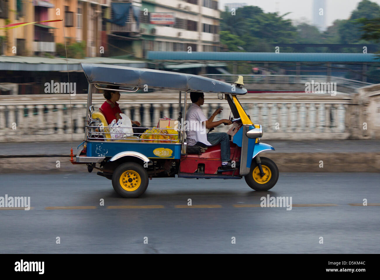 The tuktuk is an open sided taxi with a small engine  used by the city dwellers of Bangkok. - Stock Image