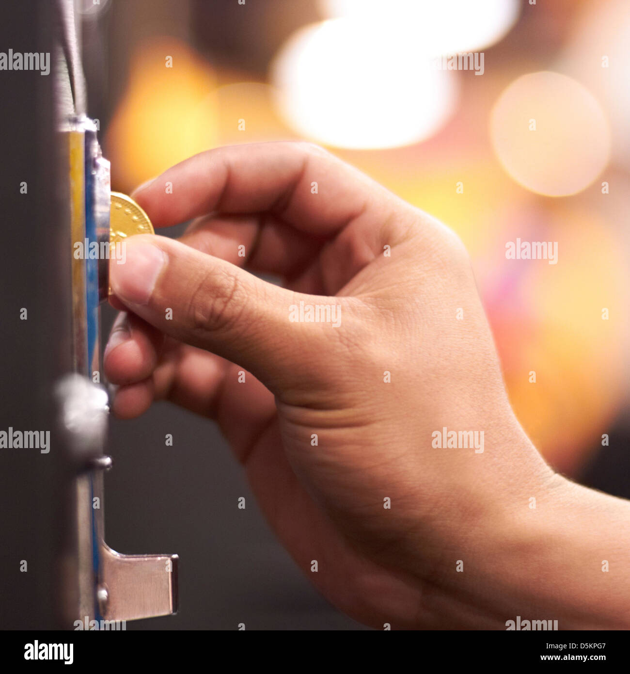 Hand inserting coin into machine - Stock Image