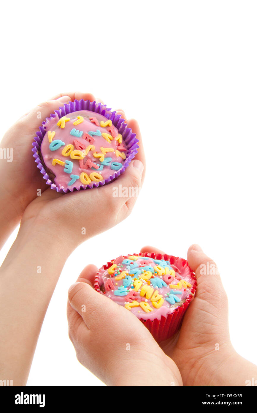 Two decorated cupcakes holding in child hands over white - Stock Image