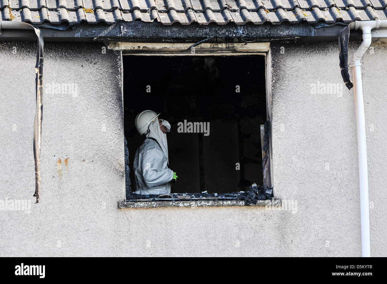 Fire investigation officers examine the scene of a fatal house fire to determine the cause of the incident. - Stock Image