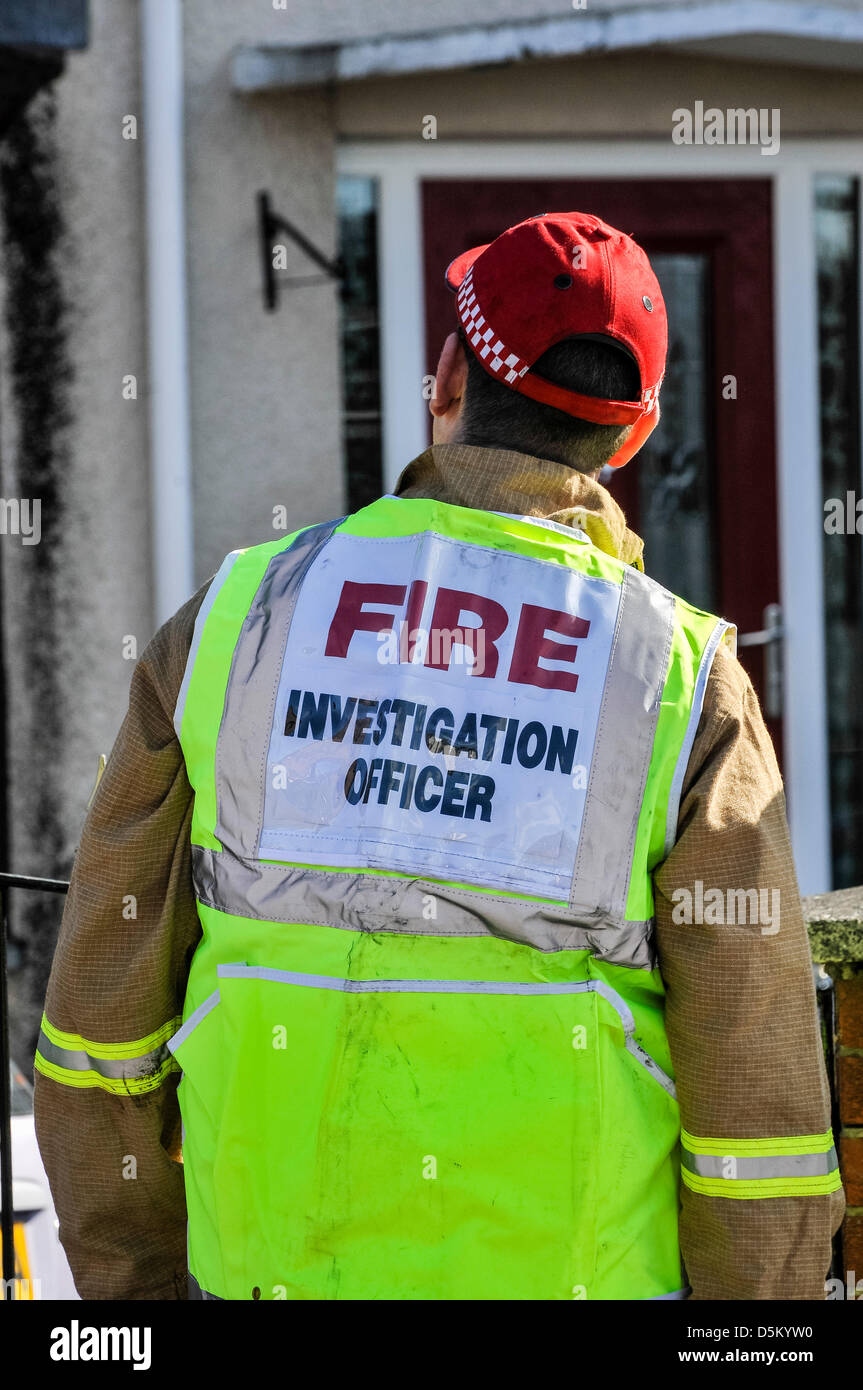 A fire investigation officer examines a fatal house fire. - Stock Image