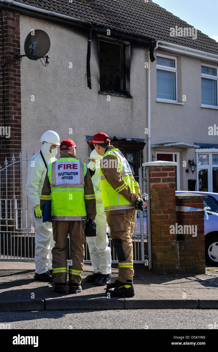 Fire investigation officers begin their examination of a fatal house fire. - Stock Image