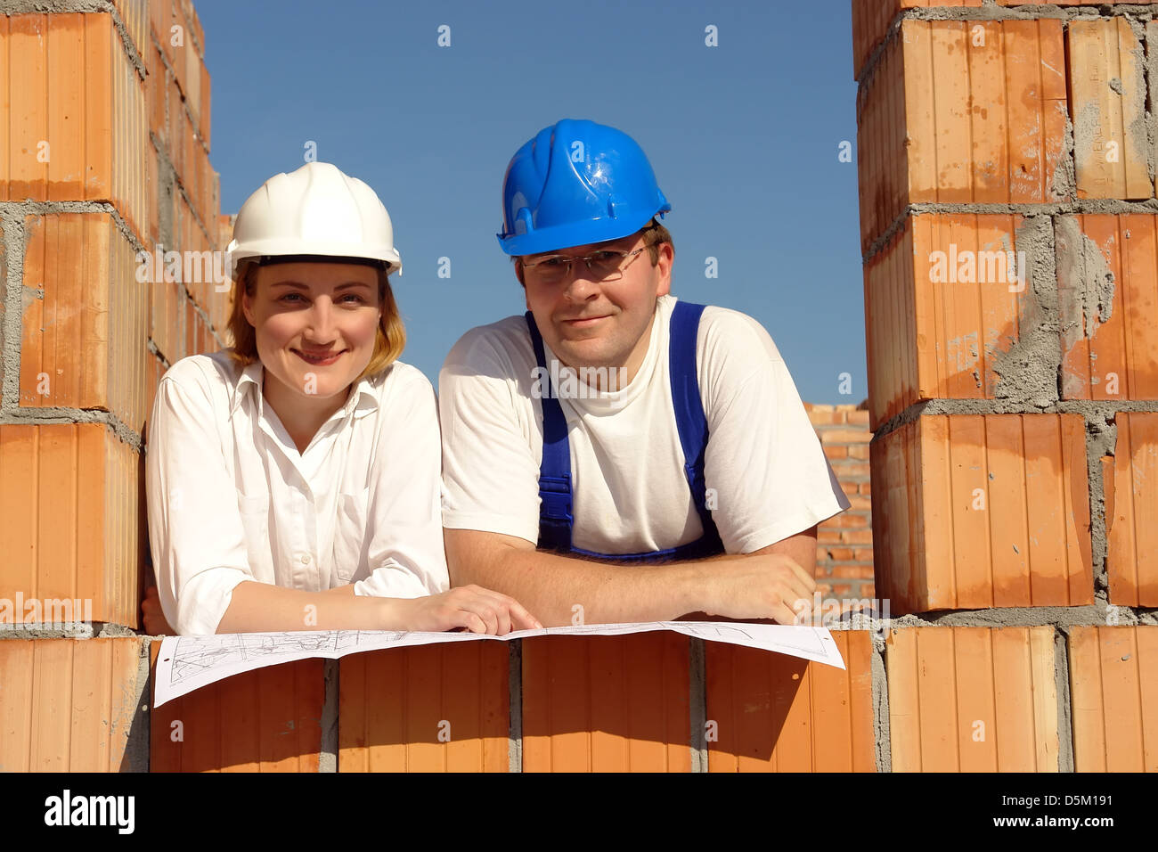 Couple wearing hard hats posing in their future house window opening resting on building plan - Stock Image
