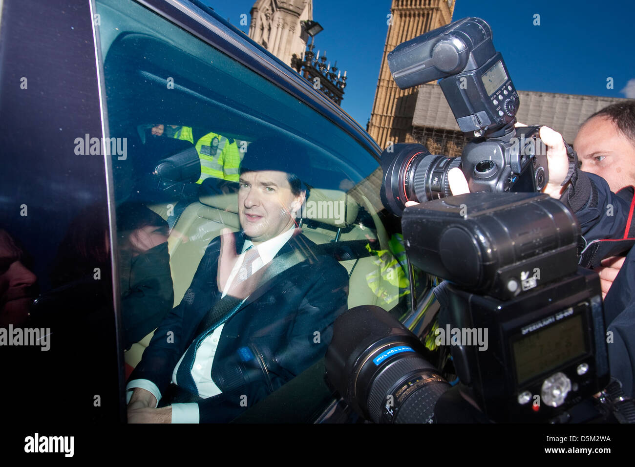 George Osborne, Chancellor of the Exchequer leaving the Houses of Parliament whilst press take pictures through - Stock Image