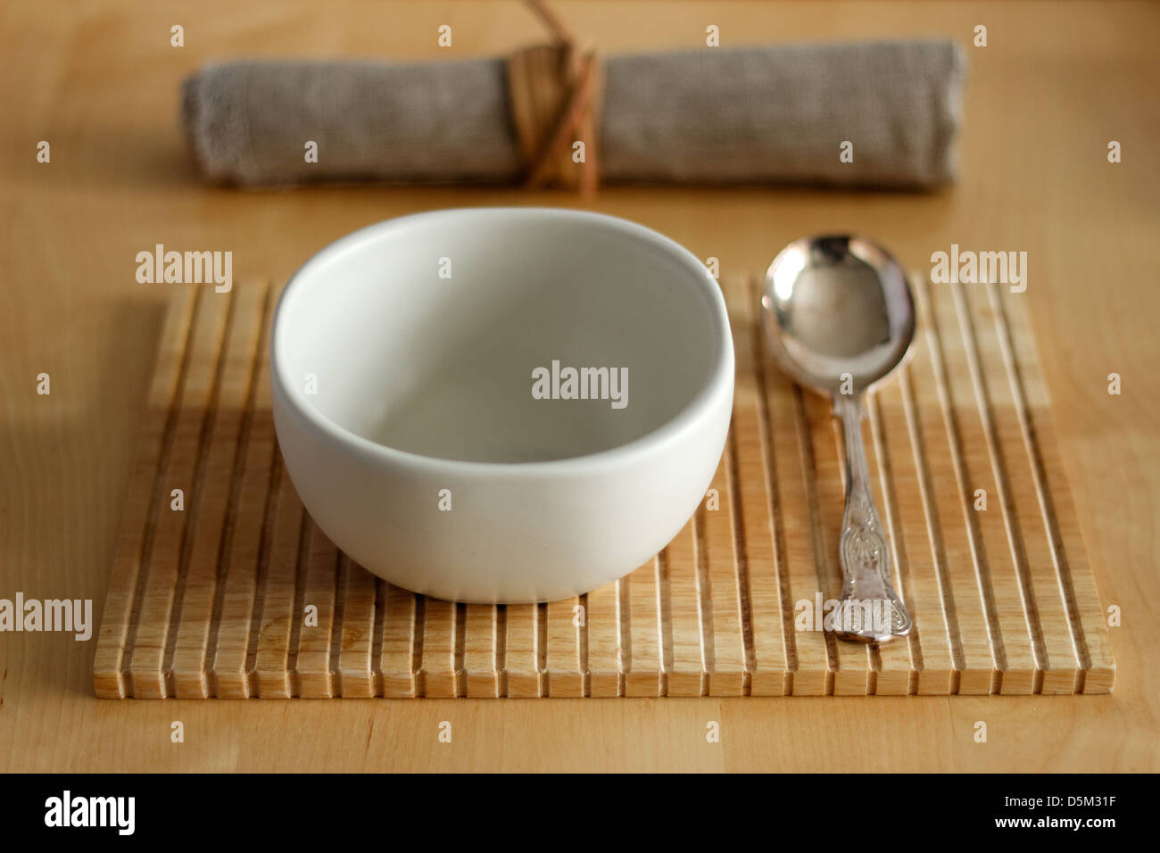 Empty bowl with spoon and napkin - Stock Image