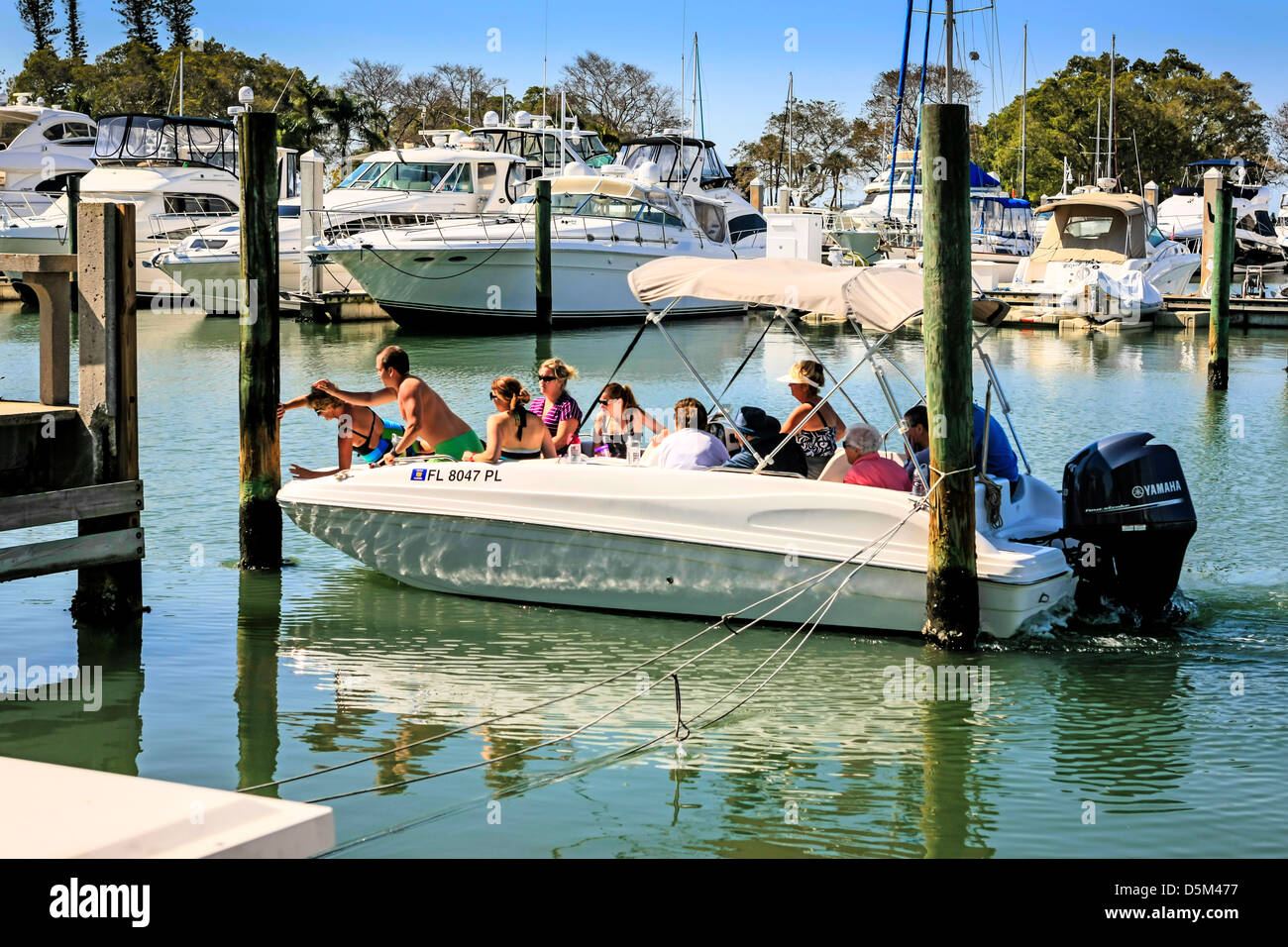 People having rented a boat collide with a mooring pole in Sarasota marina FL - Stock Image