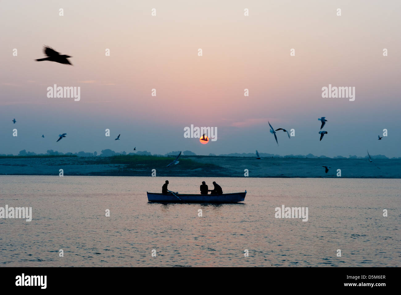 Tourists watch the sunrise on the River Ganges/Ganga at Varanasi. - Stock Image