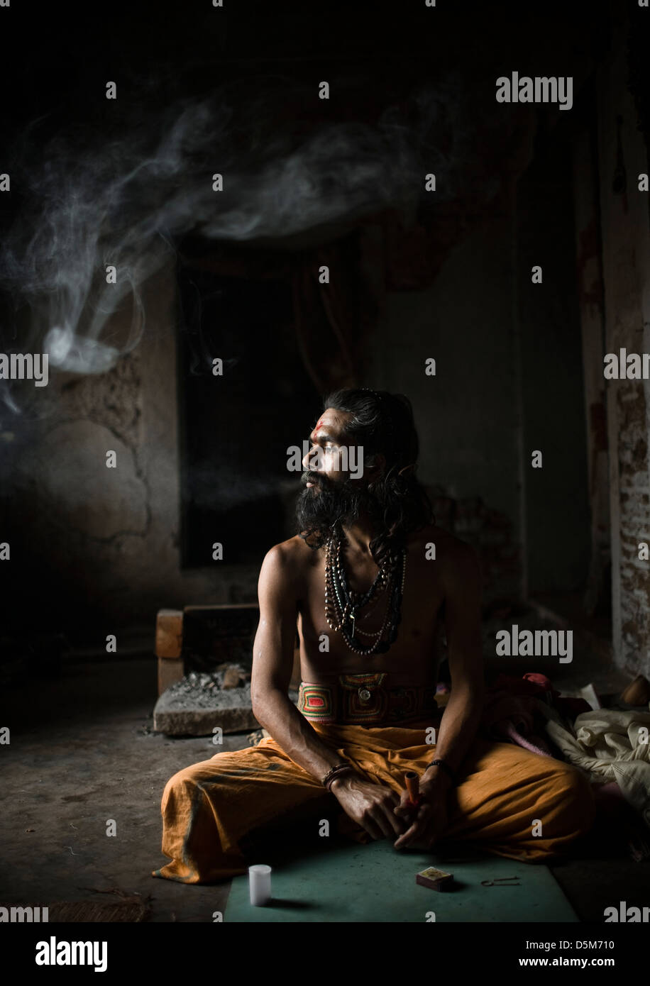 Sadhu smoking marihuana at his home in Varanasi Stock Photo