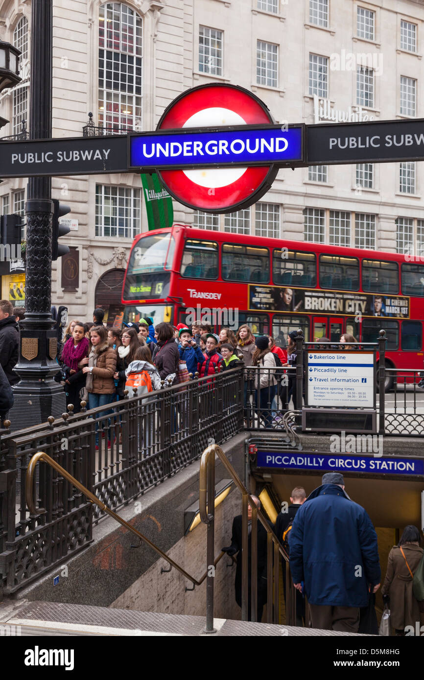 Piccadilly Circus Underground station entrance and London red bus. - Stock Image