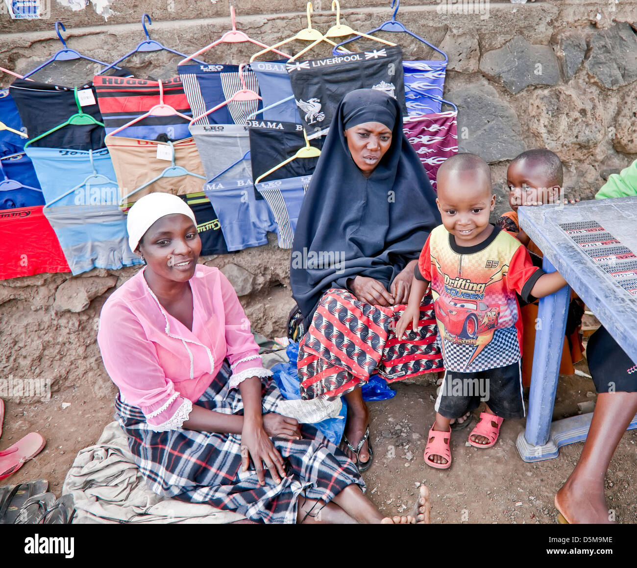 Two Muslim women on market with baby in Moshi; Africa;East Africa;Tanzania;young and older women - Stock Image