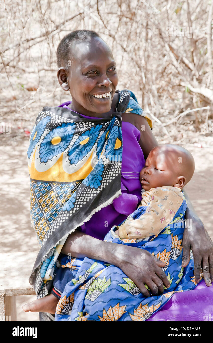 Maasai mother with young infant baby outdoors in Africa;East Africa;Tanzania; - Stock Image