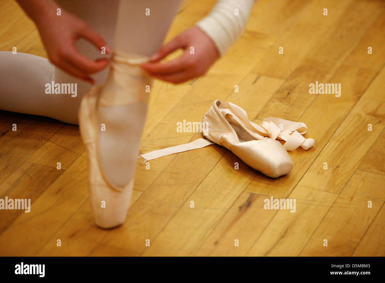 young female ballet student putting on pointe shoes at a ballet school in the uk - Stock Image