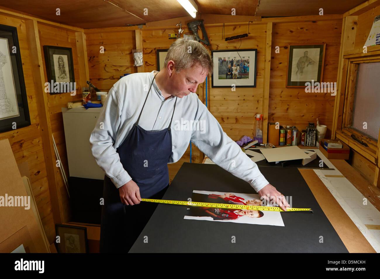 framer measuring prints for framing in a framing workshop - Stock Image