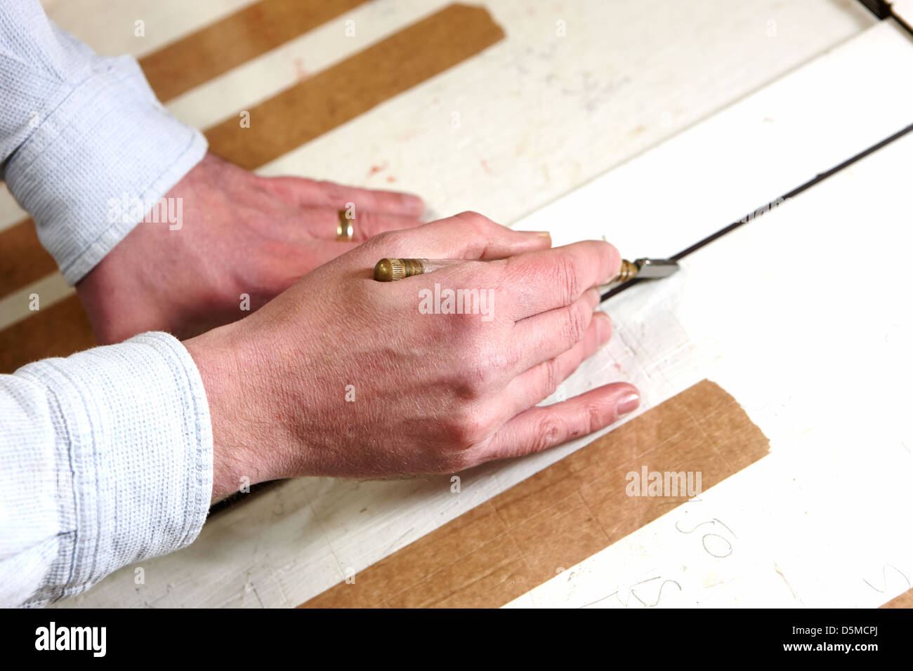 framer cutting glass by hand in a framing workshop - Stock Image