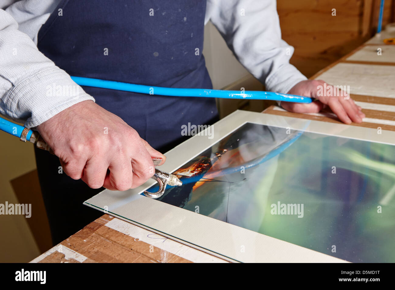 framer using air line to clean dust off a frame in a framing workshop - Stock Image