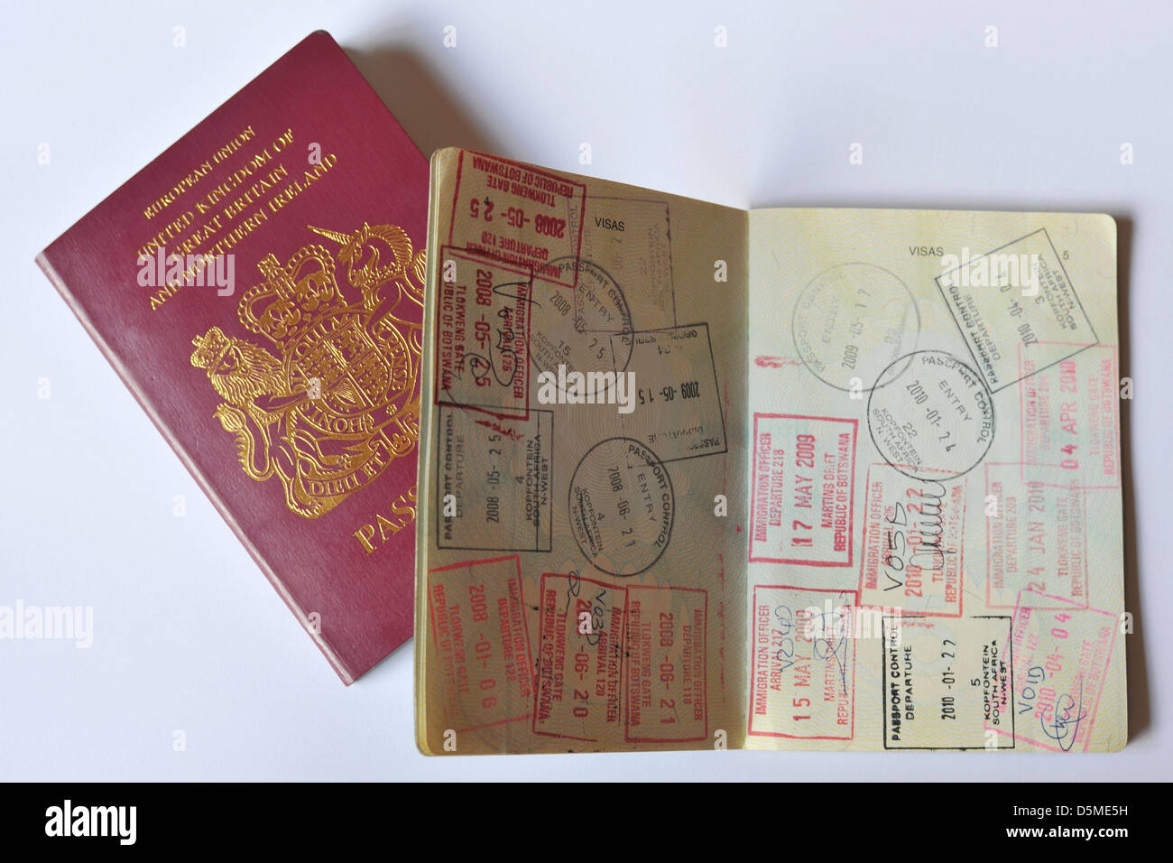 The front cover of a British Passport and a fully stamped Visa page. - Stock Image