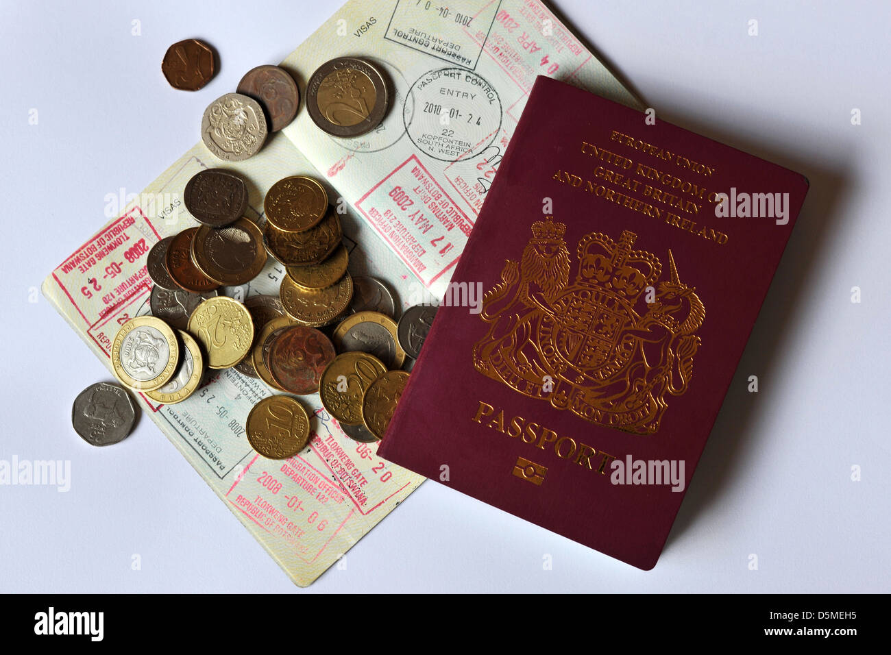 The front cover of a British Passport on top of a fully stamped Visa page covered in coins. - Stock Image