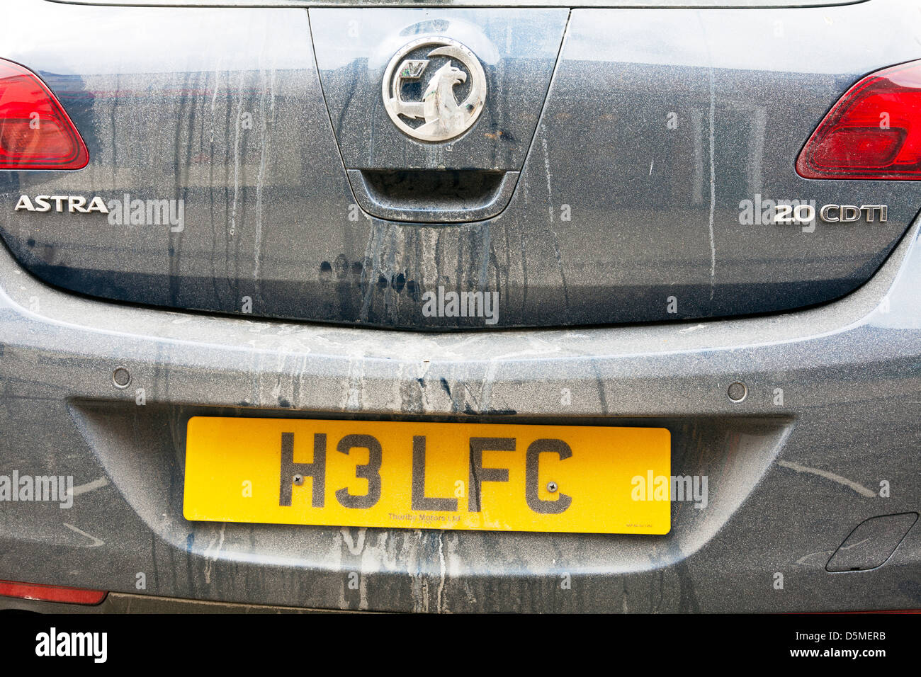 Very dirty mucky rear of car due to bad weather back end of Vauxhall Astra - Stock Image