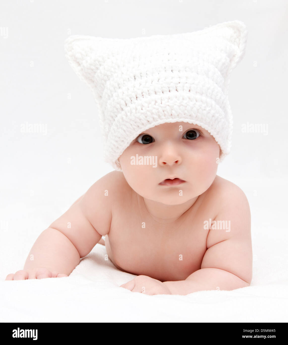 baby in white hat lies on bed - Stock Image