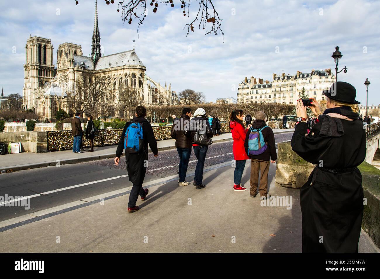 Tourists on Pont de l'Archevêché and Notre Dame Cathedral (Cathedrale Notre Dame de Paris) in the - Stock Image