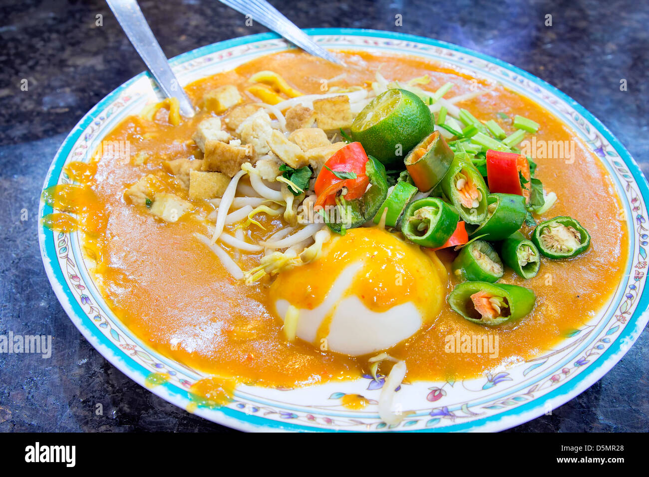 Malay Mee Rebus Noodle Dish Garnished with Cut Chili Peppers Tofu Chinese Celery and Hard Boiled Egg - Stock Image