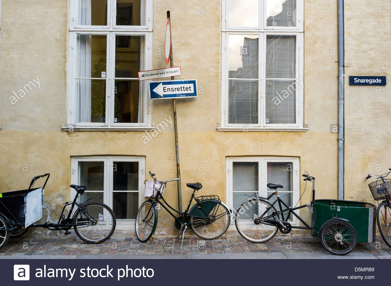Bikes lined up against a wall on a sidewalk in central Copenhagen, Region Hovedstaden, Denmark - Stock Image