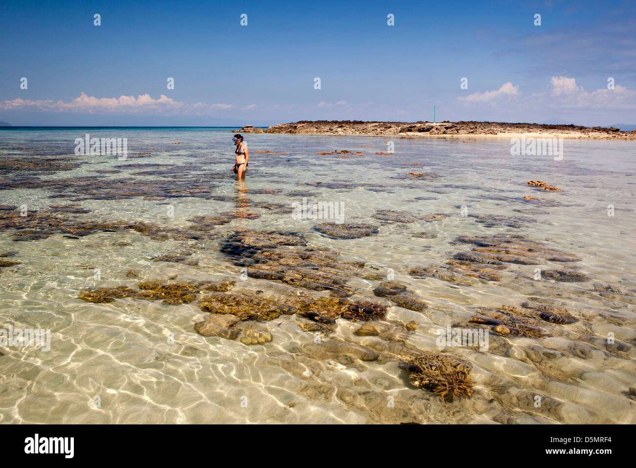 Madagascar, Nosy Be, Nosy Tanikely island snorkeller amongst coral heads off main beach - Stock Image