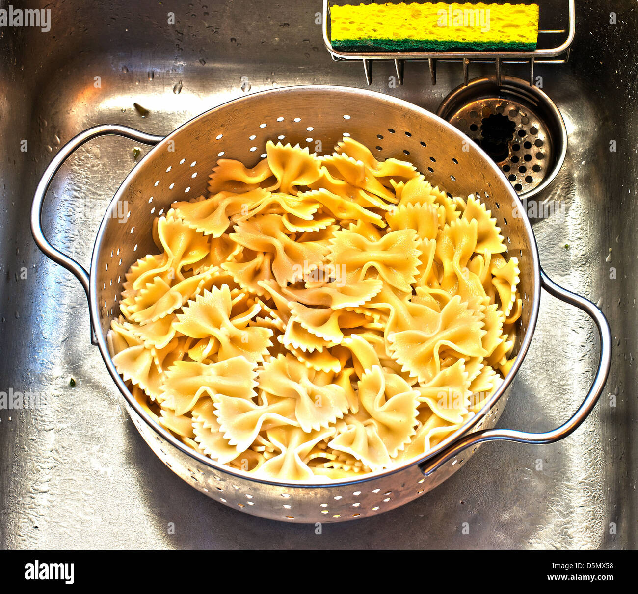 Freshly boiled Farfalle, or bow tie, pasta draining in colander in kitchen sink with bright yellow sponge. - Stock Image