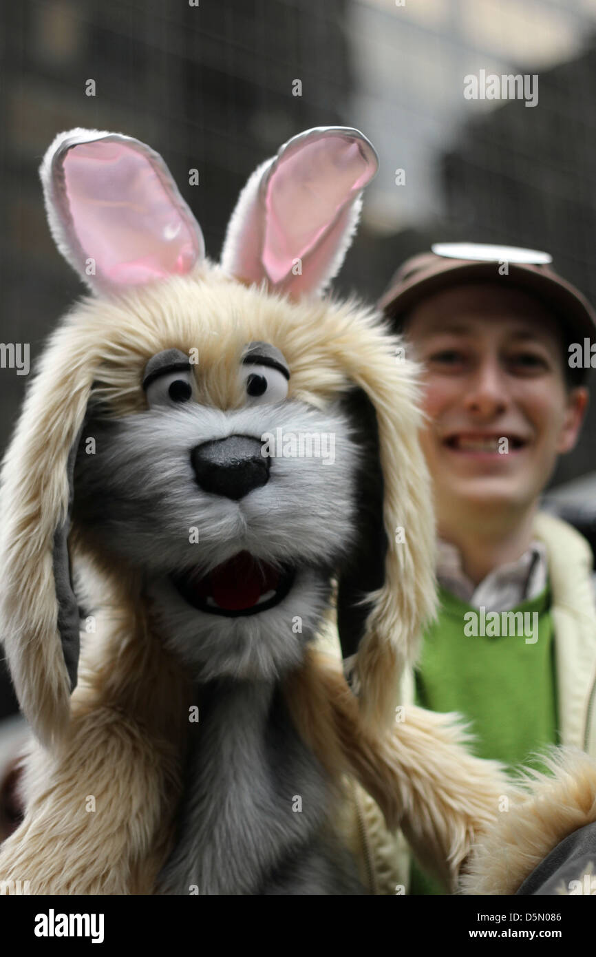 A puppet of a dog wearing bunny hears, puppeteer in the background, at New York City's Easter Parade - Stock Image