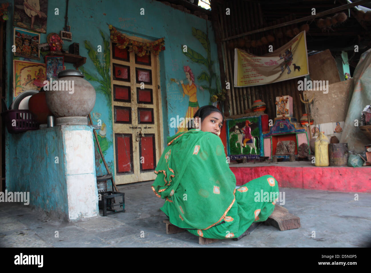 A woman peeps from the courtyard of her house in the Gulbai Tekra locality of craftsmen, idol-makers, Ahmedabad, - Stock Image