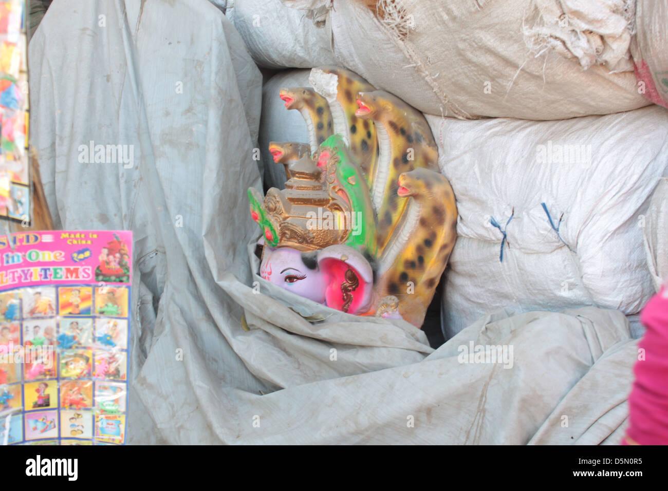 An idol of Hindu God, Ganesh, lies hidden behind sacks in the Gulbai Tekra locality of craftsmen, Ahmedabad, Gujarat, - Stock Image