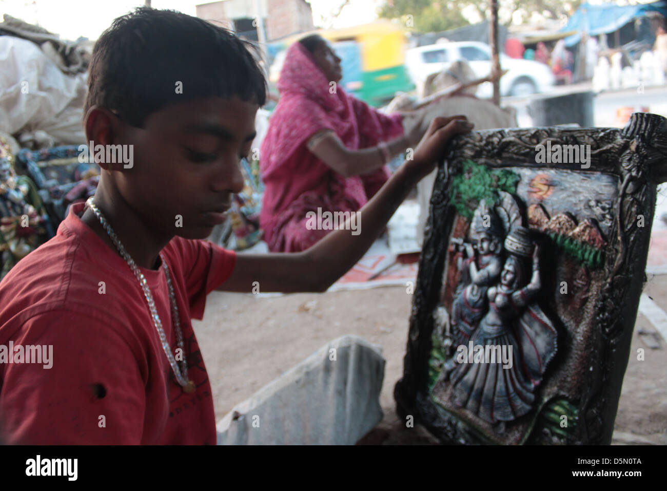 An Indian family works on completing Hindu idols in the Gulbai Tekra locality of Ahmedabad, Gujarat, India. - Stock Image
