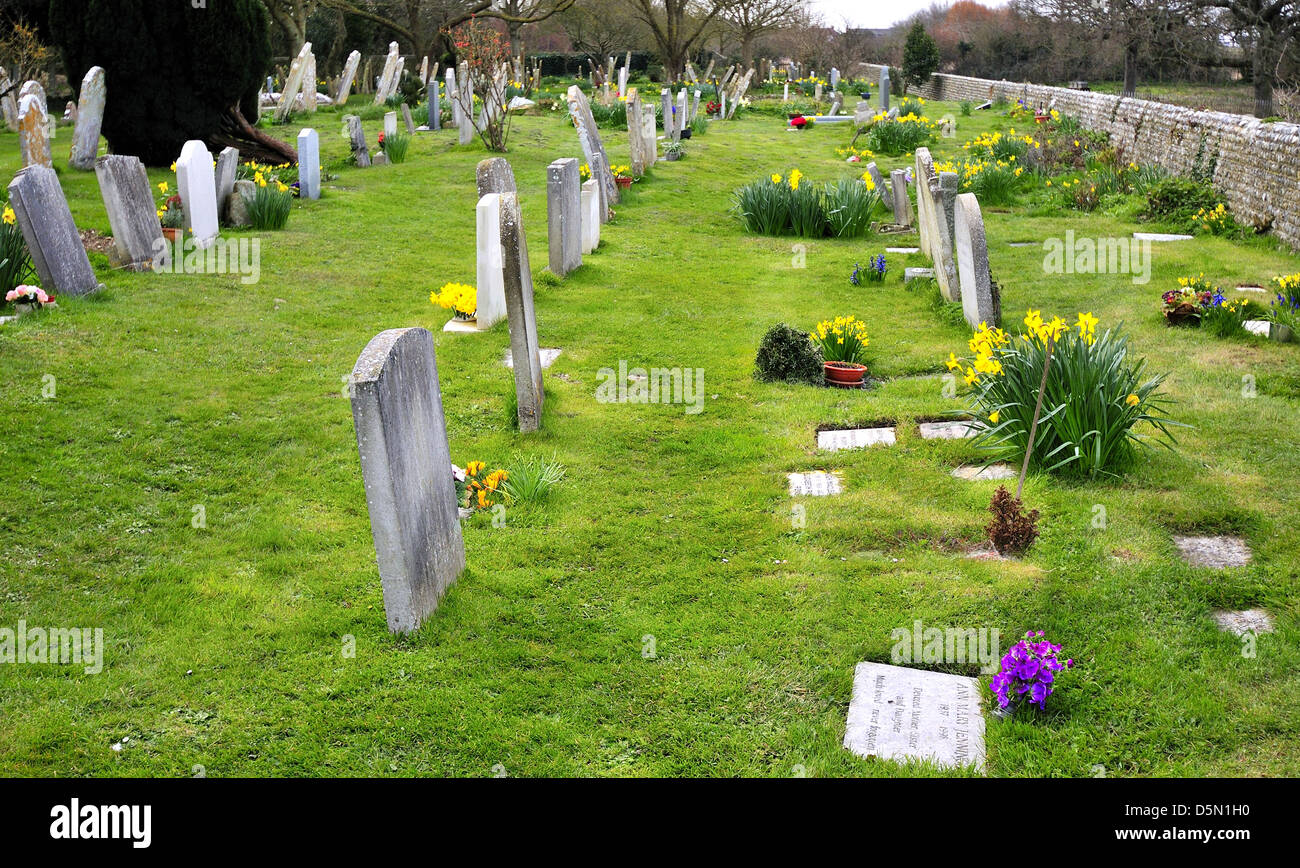 Graveyard at West Wittering  church  with  seeded wild daffodils   in bloom during  Easter weekend - Stock Image