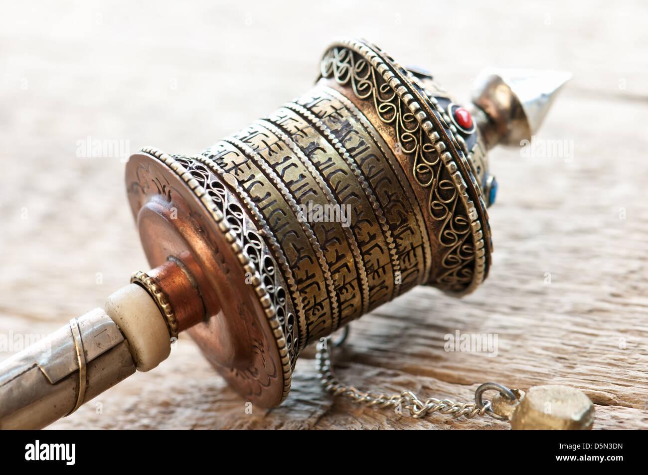 gold tibetan spool on table - Stock Image