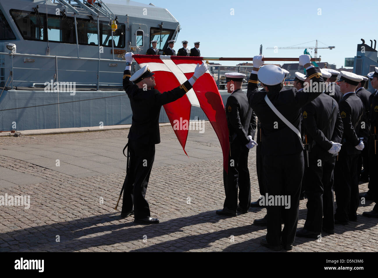 Copenhagen, Denmark. April 4th 2013. Cadets from the Royal Danish Naval Academy roll the naval flag after a parade - Stock Image