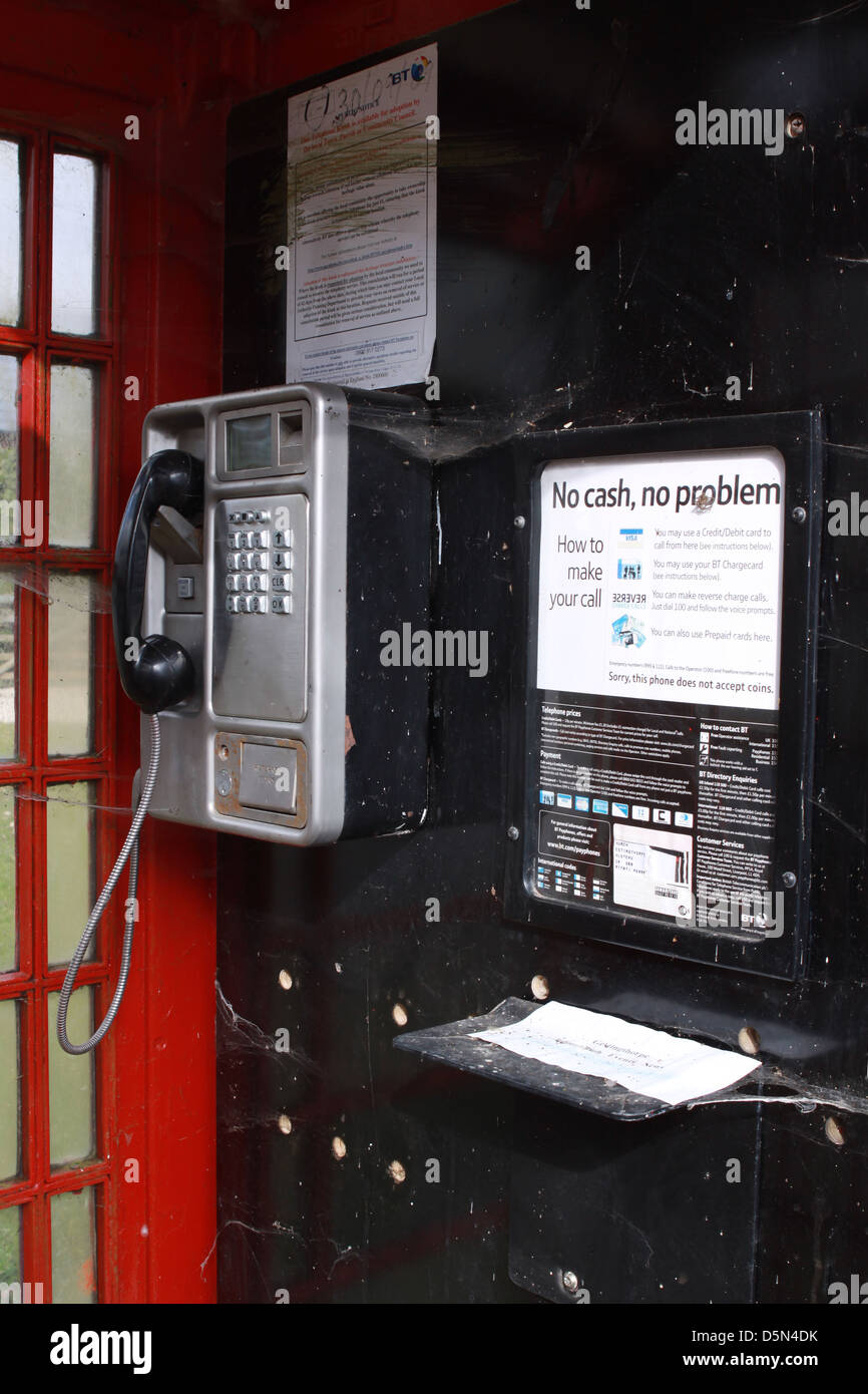 active yet unused rural phone box covered in cobwebs and dirt. includes instructions on how to make a telephone - Stock Image