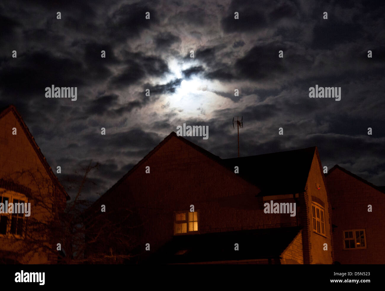 Spooky moon over English house - Stock Image