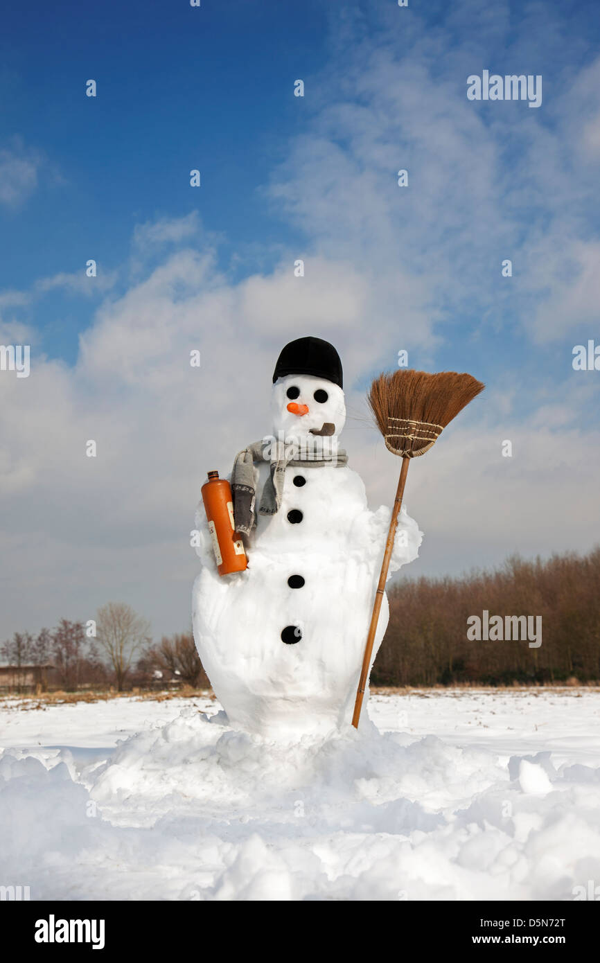 Decorated happy snowman with carrot nose, hat, pipe, scarf and broom in the snow in winter - Stock Image