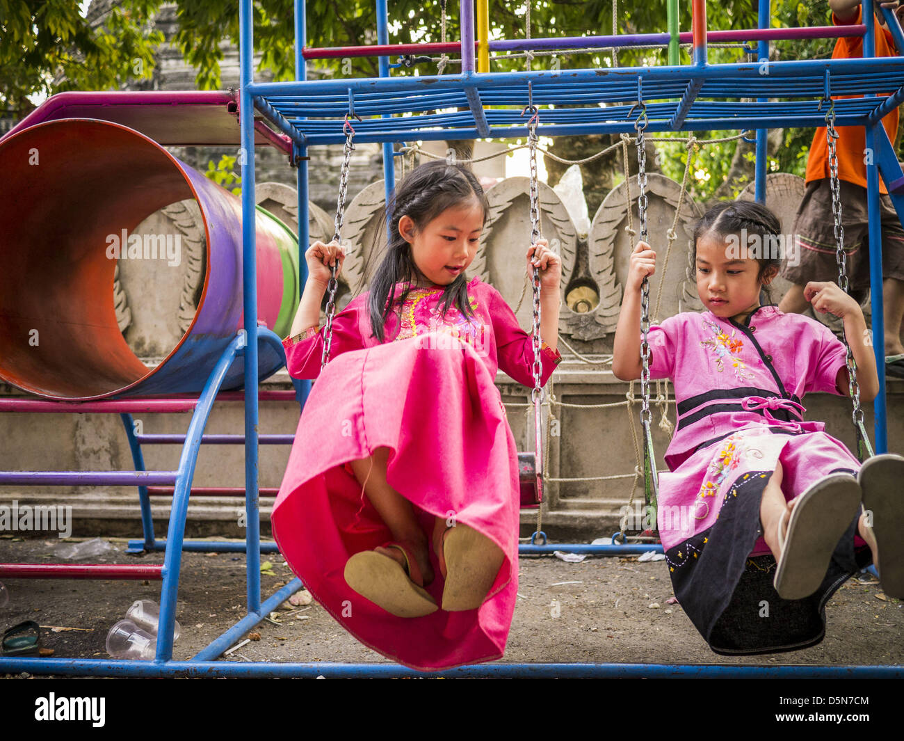 Chiang Mai, Thailand. 5th April 2013. Thai girls in traditional clothes play on a swing set at Wat Pa Pao. Their Stock Photo