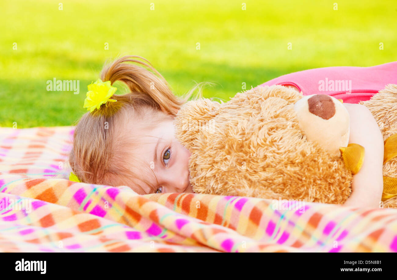 Sweet small girl laying down on the meadow with big soft toy, happy childhood, day care, spring time fun - Stock Image